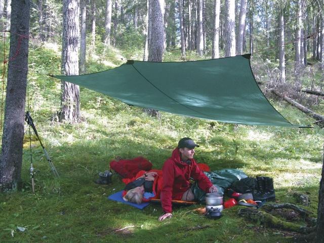 ヒルバーグの緑のタープの下に赤い服の男性