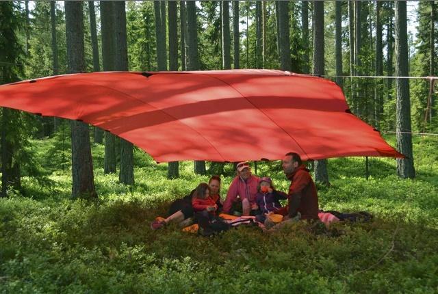 ヒルバーグの赤いタープの下で家族5人がリラックス