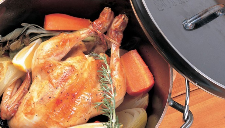 ダッチオーブンで丸鶏を料理している