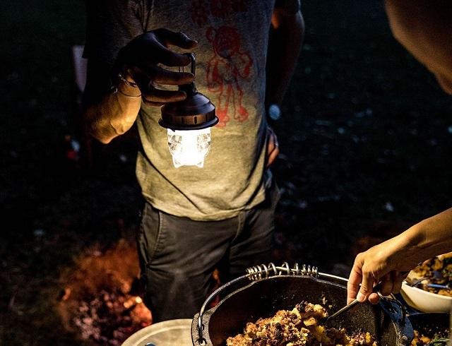ベアボーンズリビング ビーコンカラビナライトを手に下げて料理を照らしている