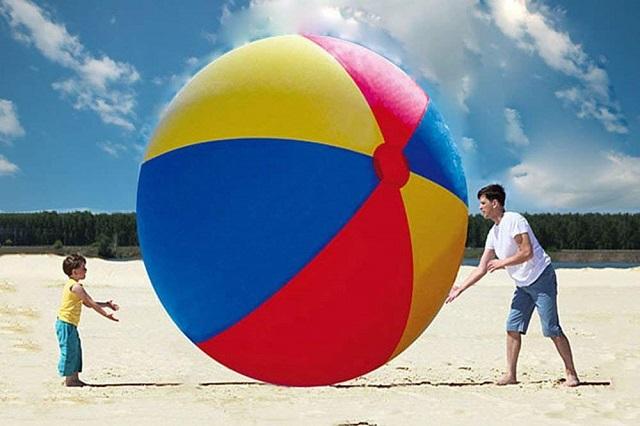 パパと子供が大きなビーチボールで遊ぶ様子