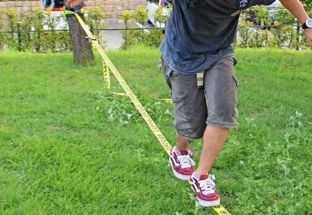 男性がDOD(ディーオーディー) バランスウォーカー スラックラインの上でバランスをとっている