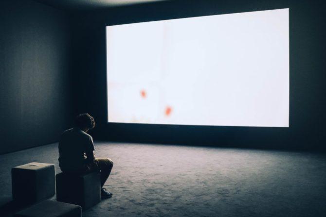 白いスクリーンを見る男性