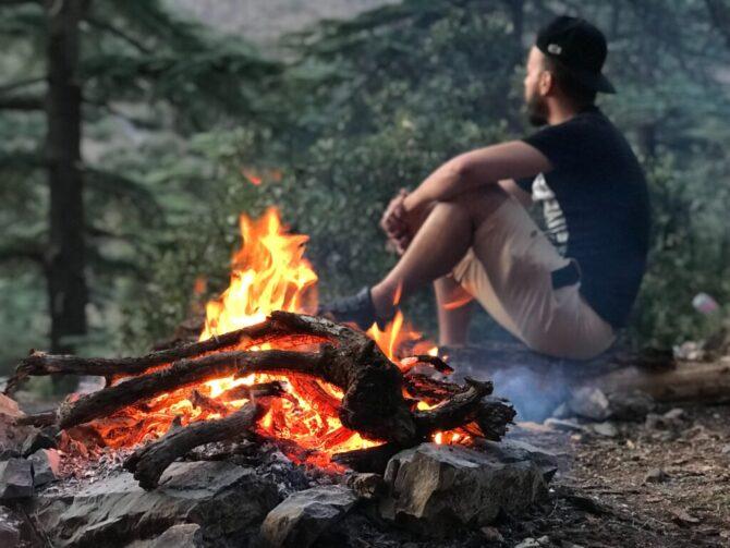 焚き火の横で佇む男性